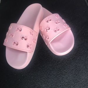 Baby pink Gucci slides.